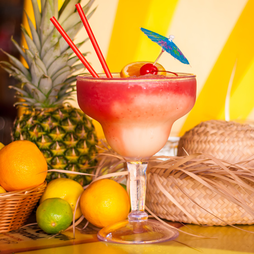 36oz Blended Strawberry Mega Margarita with citrus fruit, pineapple and sombrero on table