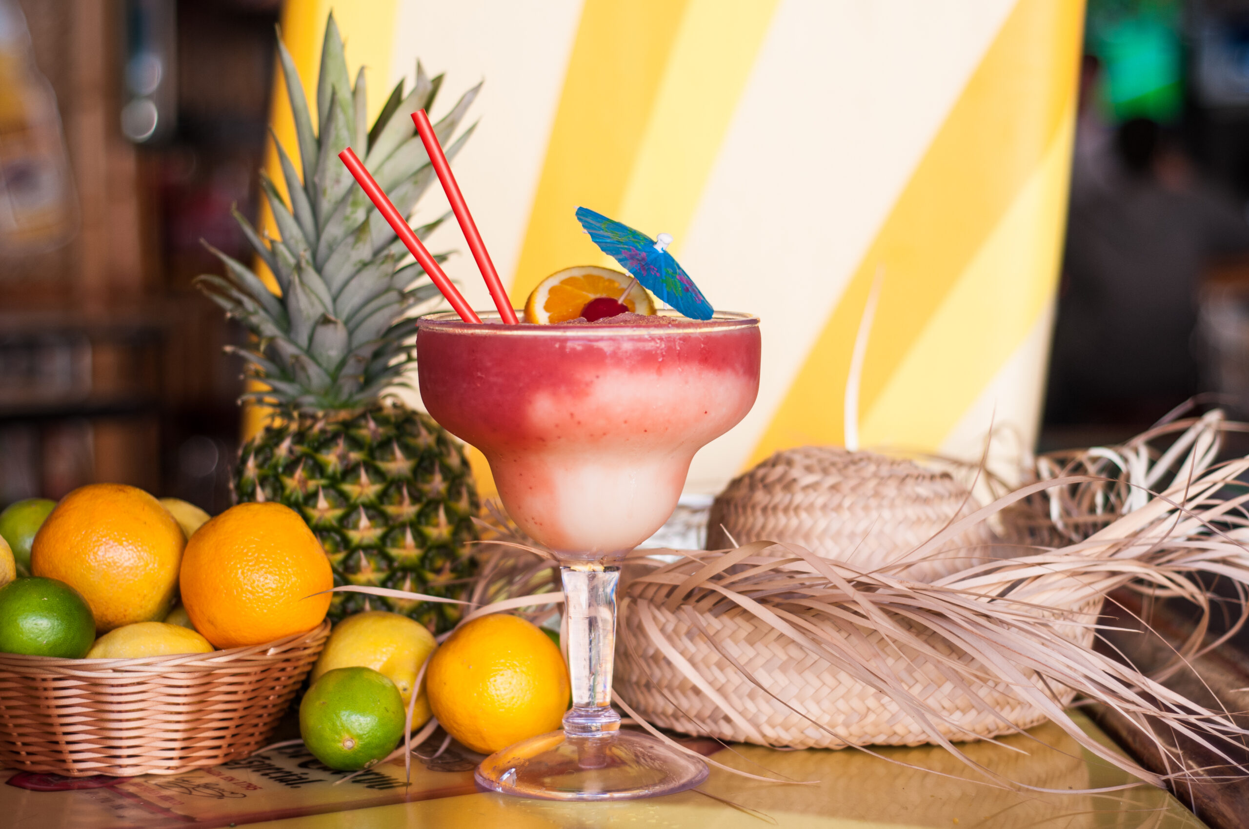 Red and peach Mega margarita surrounded by fruit and a sombrero